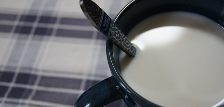 Tasse auf Tischdecke mit Milch