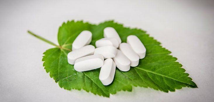 Tabletten auf grünem Blatt als Symbol für Hausmittel