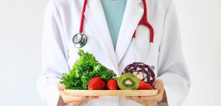 Arzt hält einen Teller mit Obst und Gemüse in der Hand