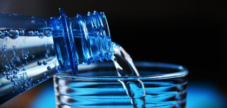 Wasser aus Flasche wird in Glas zum Trinken vorbereitet